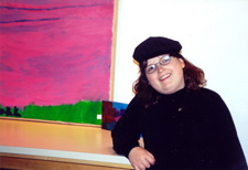 Eve standing next to her painting