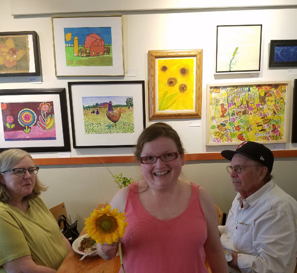 Alt Text = Evita in orange top, holding a sunflower, standing by sunflower painting