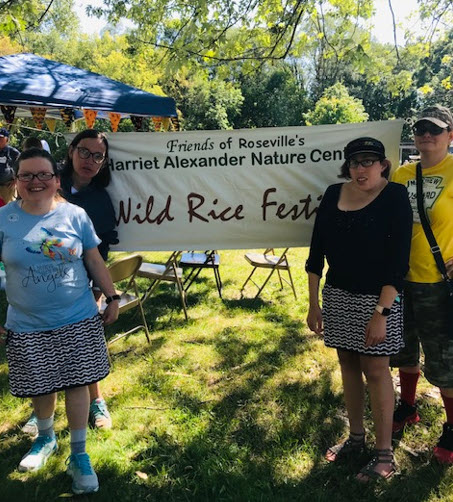 alt text = 4 women standing outdoors by Wild Rice Festival Banner